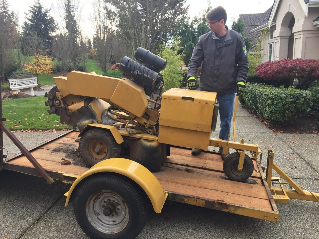 Jim Folger unloading the stump grinder in preparation for removing a tree stump.